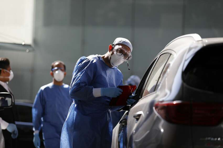 A doctor gathers information from a driver arriving to get tested for COVID-19 at private laboratory Biomedica de Referencia, in the Lomas Virreyes neighborhood in Mexico City, Thursday, March 26, 2020. (AP Photo/Rebecca Blackwell)