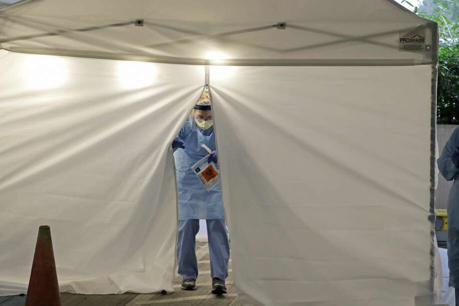 A nurse at a drive up COVID-19 coronavirus testing station set up by the University of Washington Medical Center exits a tent while holding a bag containing a swab used to take a sample from the nose of a person in their car, Friday, March 13, 2020, in Seattle. UW Medicine is conducting drive-thru testing in a hospital parking garage and has screened hundreds of staff members, faculty and trainees for the COVID-19 coronavirus. U.S. hospitals are setting up triage tents, calling doctors out of retirement, guarding their supplies of face masks and making plans to cancel elective surgery as they brace for an expected onslaught of coronavirus patients. (AP Photo/Ted S. Warren) Photo: Ted S. Warren/AP / Copyright 2020 The Associated Press. All rights reserved.