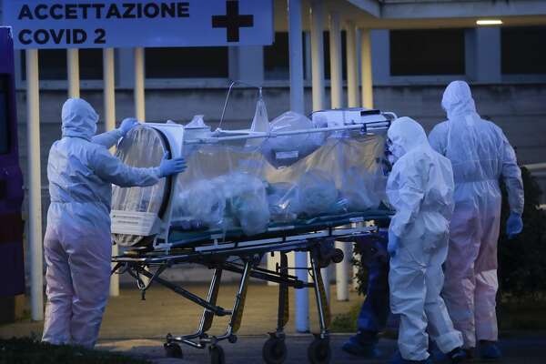 """A patient in a biocontainment unit is carried on a stretcher at the Columbus Covid 2 Hospital in Rome, Monday, March 16, 2020. The new Columbus Covid 2 Hospital, an area fully dedicated to the COVID-19 cases at the Gemelli university polyclinic, opened today with 21 new ICU units and 32 new beds, in order to support the regional health authorities in trying to contain the pandemic. Sign at top in Italian reads """"Admission COVID 19"""". For most people, the new coronavirus causes only mild or moderate symptoms. For some it can cause more severe illness, especially in older adults and people with existing health problems. (AP Photo/Alessandra Tarantino)"""
