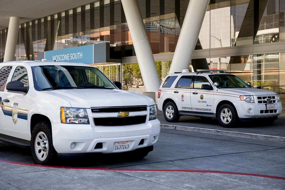 A vehicle owned by California Governor's Office of Emergency Services (left) and San Francisco's Department of Emergency Management are seen parked outside Moscone Center on Howard Street as personnel move in and out of the building in San Francisco, Calif. Thursday, March 26, 2020. San Francisco is currently using Moscone Center as their emergency operations center as residents shelter-in-place due to the outbreak of the Coronavirus.