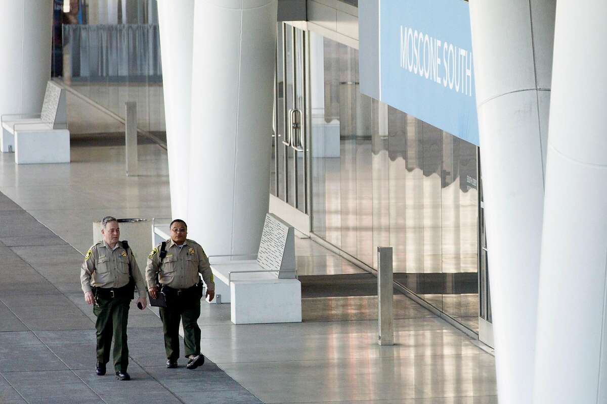 Sheriff's deputies patrol the perimeter of Moscone Center on Howard Street in San Francisco, Calif. Thursday, March 26, 2020. The City and County of San Francisco is currently using Moscone Center as their emergency operations center as residents shelter-in-place due to the outbreak of the Coronavirus.