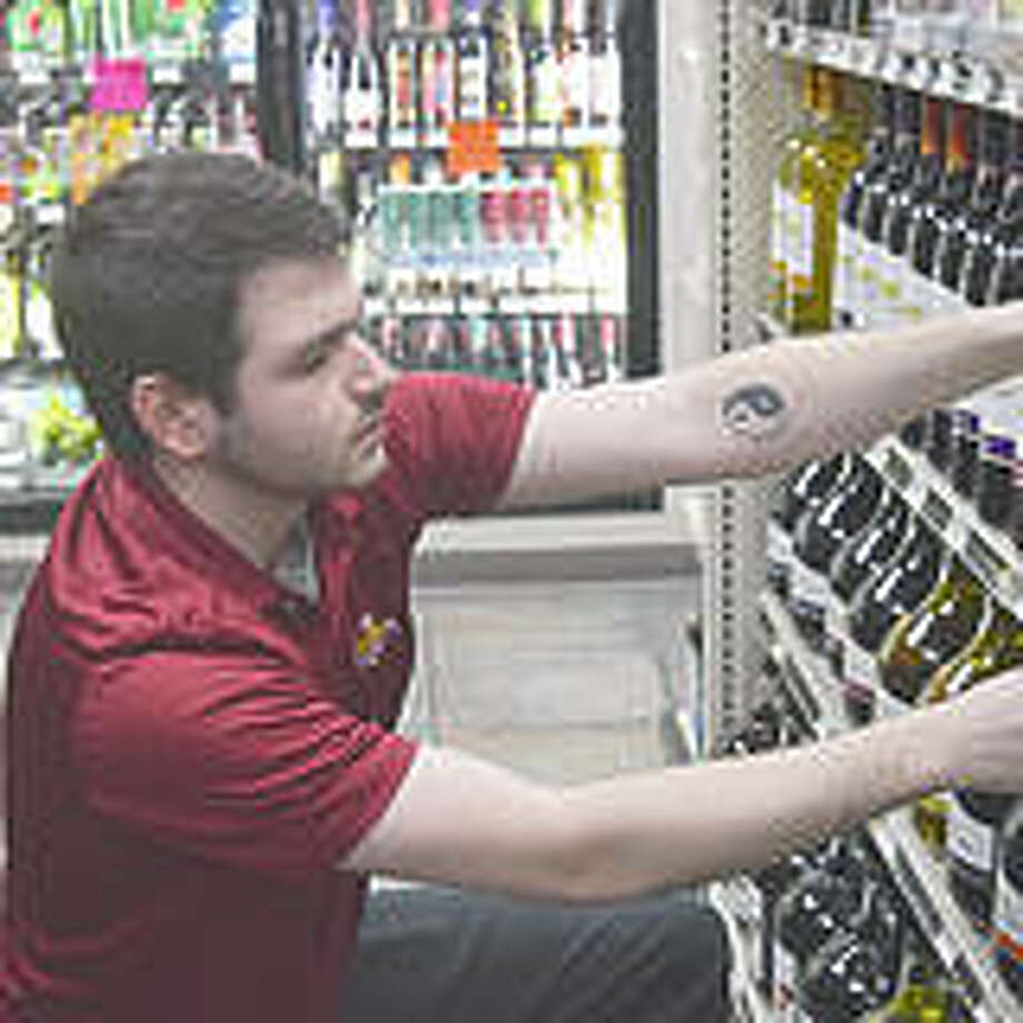 Isaac Ingram, an employee at Top Shelf Liquor, stocks beverages at the store. Liquor stores are allowed to remain open under Illinois' stay-at-home order, which mandates that only businesses deemed essential continue doing business.