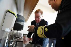 U.S. Surgeon General Vice Admiral Jerome M. Adams demonstrates how long to wash hands with Connecticut Gov. Ned Lamont during a visit the Connecticut State Public Health Laboratory, Monday, March 2, 2020, in Rocky Hill, Conn.