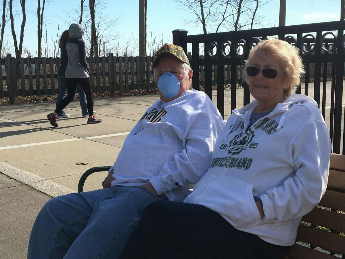 West Haveners Barry, left, and Linda, who did not want to divulge their last name, take in some sunshine and fresh air and watch the world go by in West Haven's Old Grove Park, just off the boardwalk, on Wednesday, March 26, 2020.