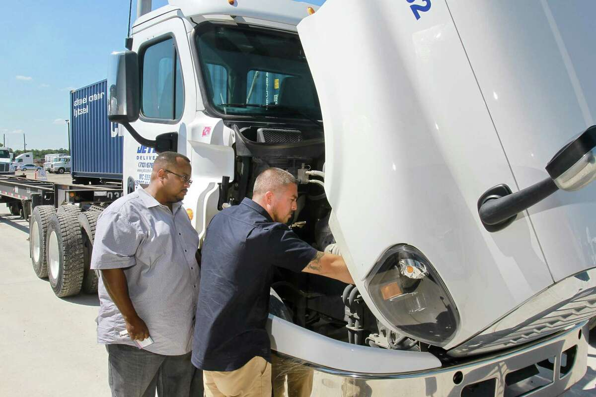 Stafford Wilson, a driver advocate, left, and Julian Leal, a driver, both for Jetco Delivery, consult during a pre-trip inspection at the Jetco Delivery facility. (For the Chronicle/Gary Fountain, September 12, 2015)