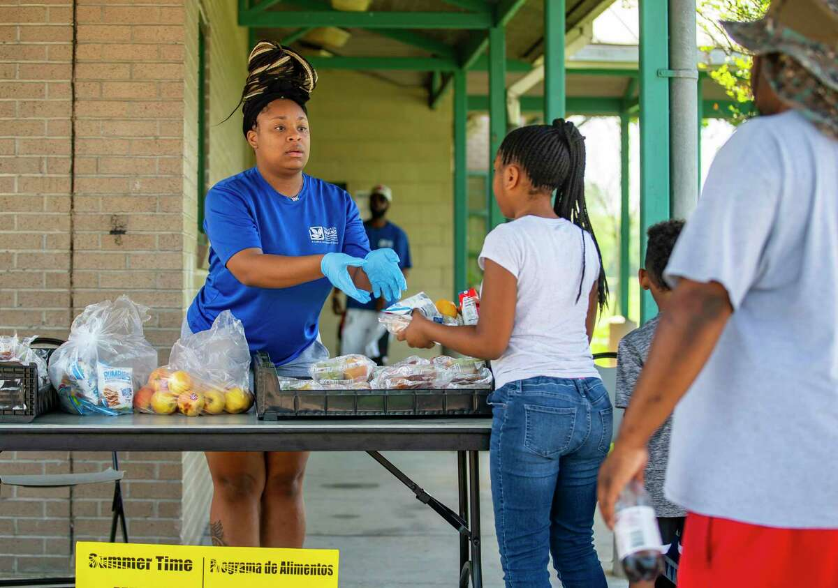 Houston Parks and Recreation employee Kristin Washington hands out meals for kids Thursday, March 26, 2020, at the Sunnyside Community Center in Houston. The city-run lunch distribution takes on added importance after Houston ISD officials announced Wednesday that they are indefinitely suspending curbside food pickup due to an individual present at a campus distribution site going under self-quarantine as a COVID-19 precaution.