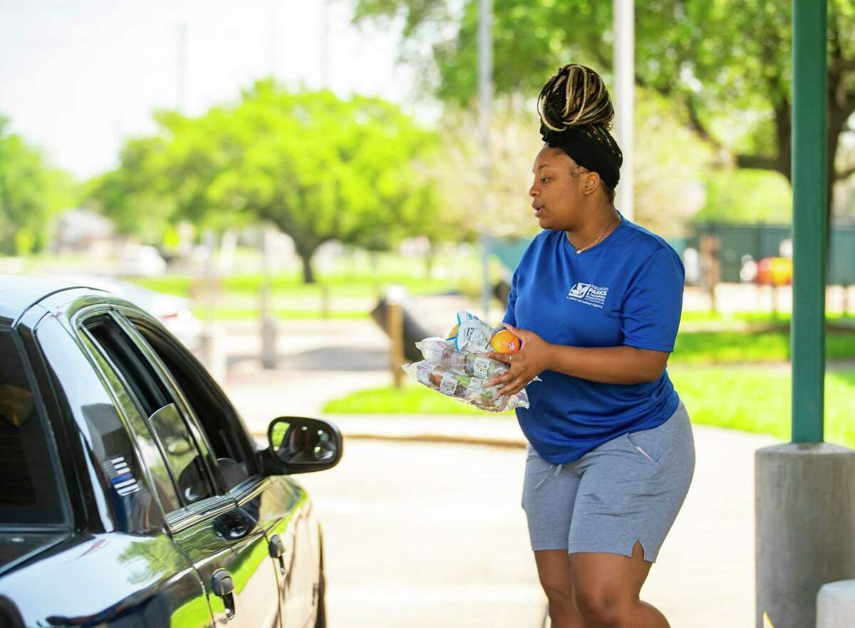 Houston Parks and Recreation employee Kristin Washington provides lunch and a snack to a family during a curbside pickup window Thursday, March 26, 2020, at the Sunnyside Community Center in Houston. City employees are providing free lunches to children each weekday from 1 p.m. to 3 p.m. amid the novel coronavirus pandemic.