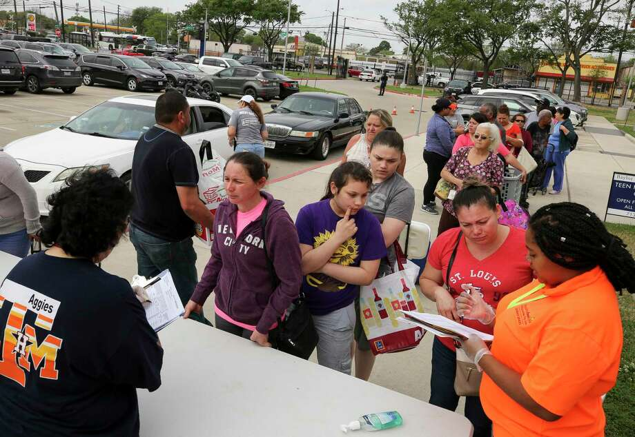 In this March 16 file photo, people wait in line to receive food at Houston ISD's Milby High School as part of the district's free food distribution plan amid school closures caused by the novel coronavirus pandemic. Photo: Godofredo A. Vásquez, Houston Chronicle / Staff Photographer / © 2020 Houston Chronicle