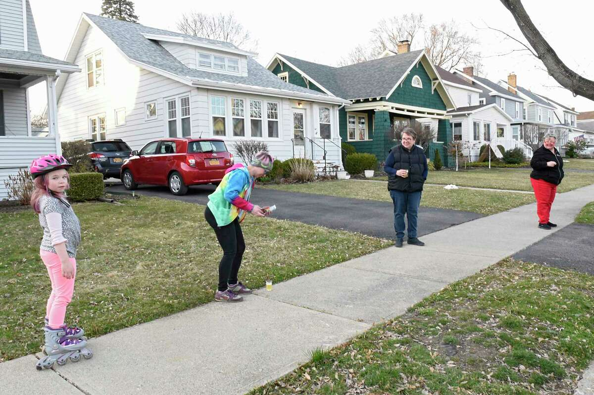 """From left, Cecilia Tanski, 7, Kate Washburn, Gretchen Brown, and Amy Whitman practice social distancing as neighbors on Fleetwood Ave. come out of their homes to do the """"Fleetwood wave"""" on Thursday, March 26, 2020 in Albany, N.Y. For about a week, the neighbors on this stretch of Fleetwood Ave. come out of their homes at 6:15 PM, wave at each other and mingle from a safe distance. (Lori Van Buren/Times Union)"""