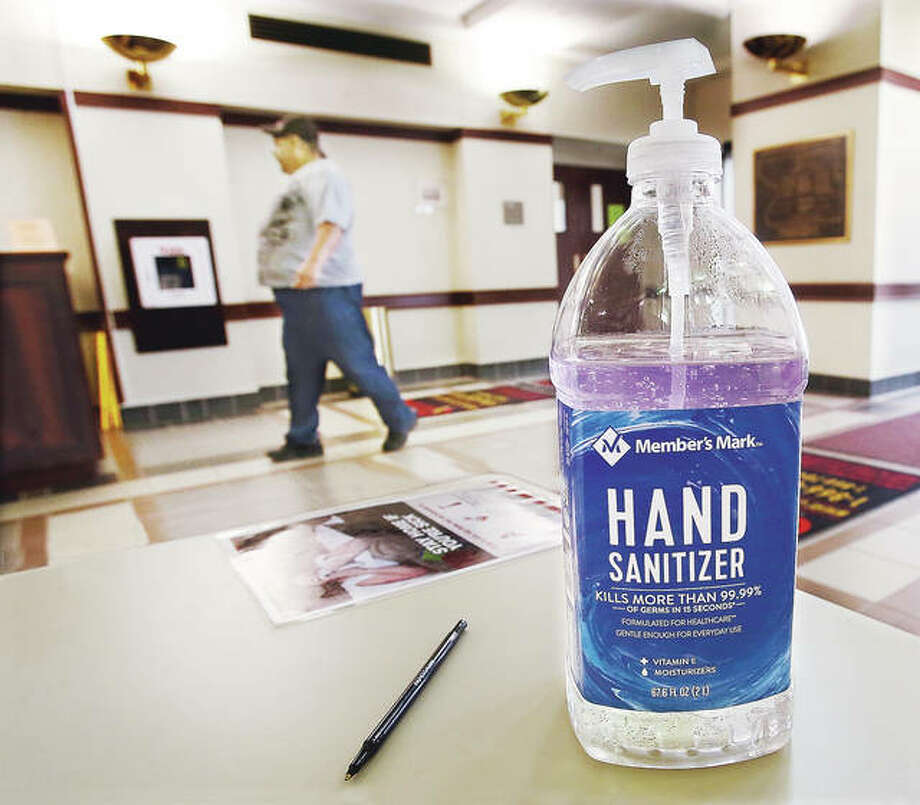 A man walks into the Madison County Administration Building in Edwardsville Thursday where visitors are met with a near industrial-sized bottle of hand sanitizer. Madison County officials want the public to know employers are hiring people to fill essential jobs while the stay-at-home order for COVID-19 is in effect.