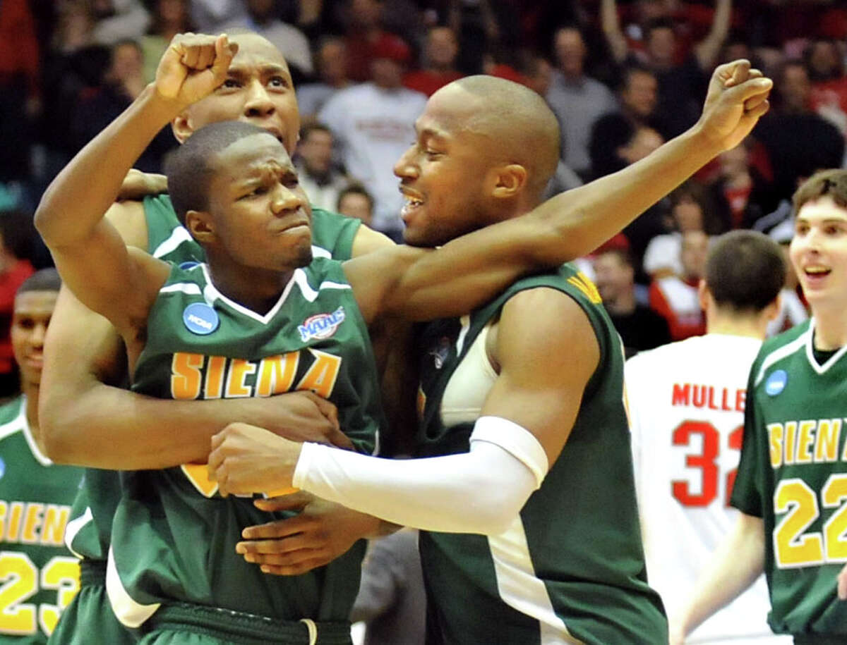 Siena's Kenny Hasbrouck, right, and Alex Franklin, back, mob Ronald Moore when he hit's a three-pointer with 3.9 seconds left in their win 74-72 over Ohio State in a double-overtime NCAA first-round game on Friday, March 20, 2009, at UD Arena in Dayton, Ohio. (Cindy Schultz / Times Union) College Sports