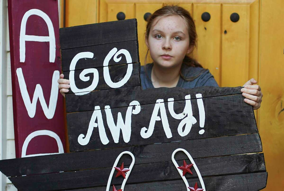 Issy Powell, 12, holds a sign she made outside her Kingwood home.