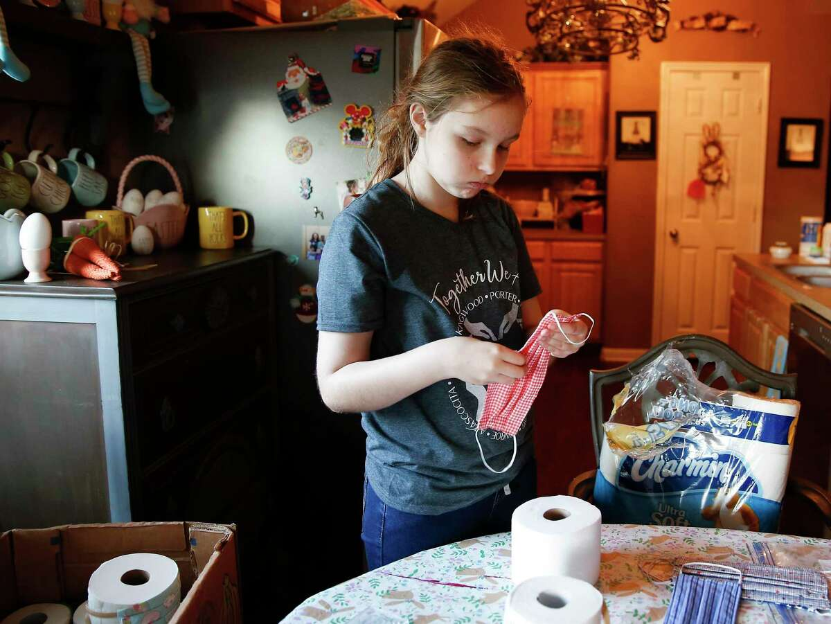 Issy Powell, 12, puts homemade face masks on rolls of toilet paper to donate.