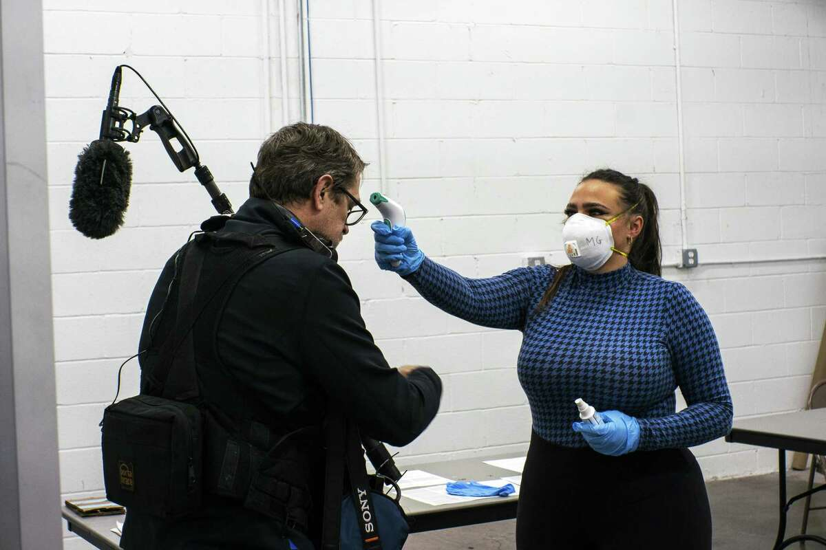 A worker takes the temperature of a journalist in New York City last week.