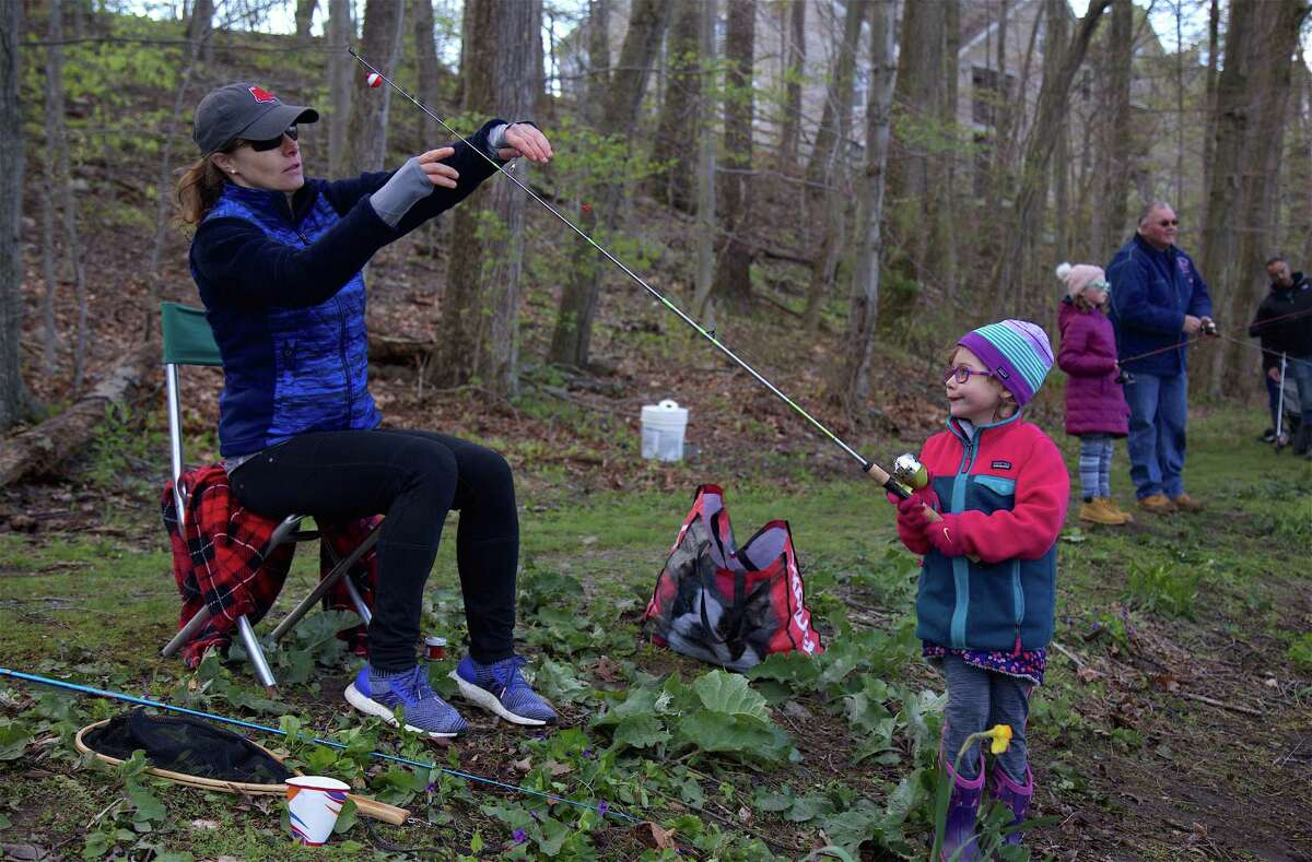 Christina Thomson of New Canaan helps her daughter Alexa, 4, with her line during a previous George Cogswell Memorial Fishing Derby.