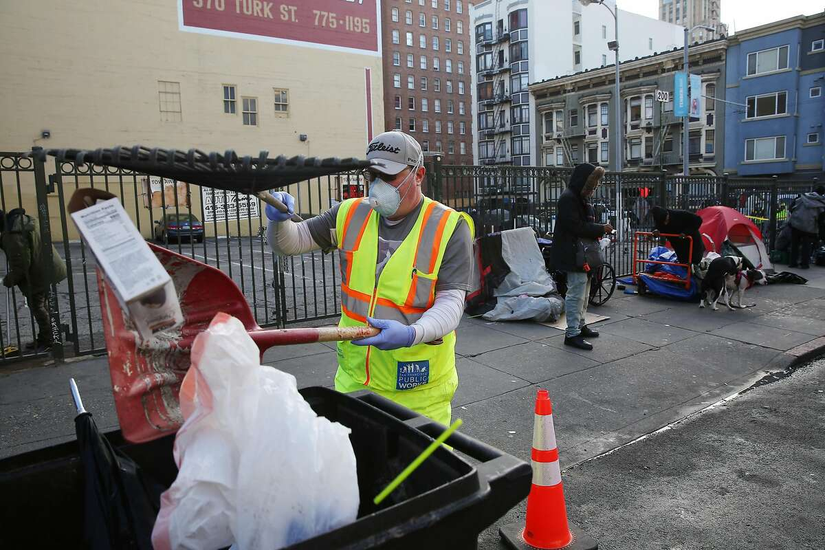 John Duport, Department of Public Works worker, places trash into a bin as he cleans the street and sidewalk along Hyde Street on Wednesday, March 25, 2020 in San Francisco, Calif.