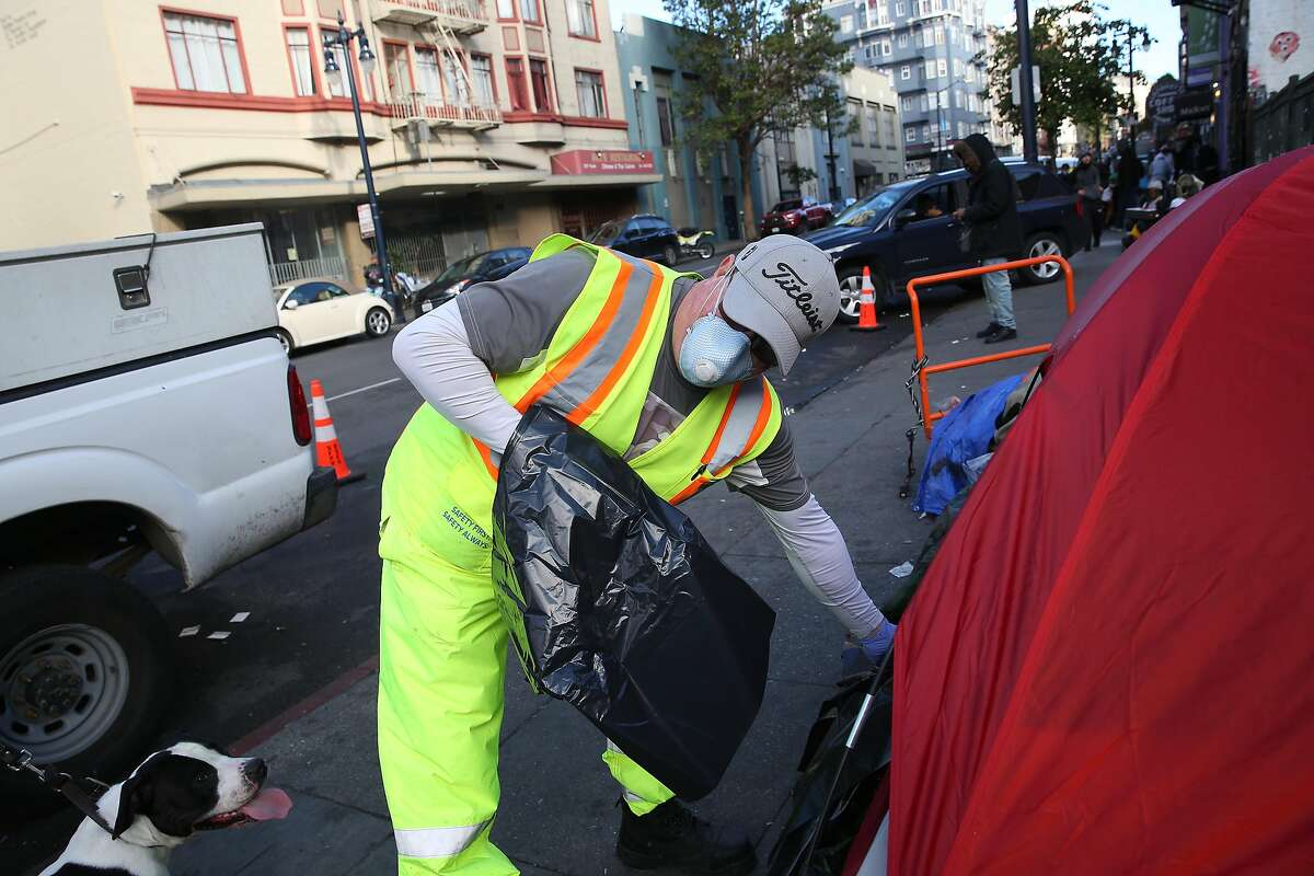 John Duport, Department of Public Works worker, hands a trash bag to someone in a tent on Hyde Street while cleaning the street and sidewalk on Wednesday, March 25, 2020 in San Francisco, Calif.