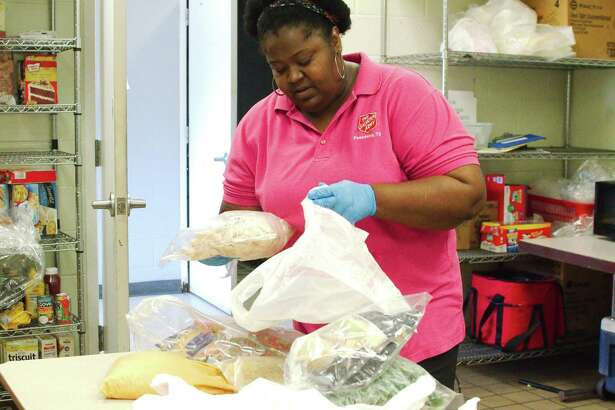 In responding to the unique needs of families during the novel coronavirus outbreak, Salvation Army social worker Anna Patterson bags pre-cooked pasta and chicken from the cooler with cheese, pre-packaged sauce, vegetables and bread in a packet that can be combined to provide a complete meal for a family of five.