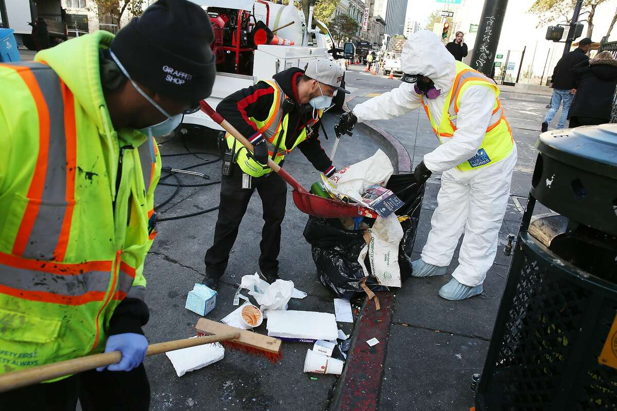 Public Works employees Palmer Lazediety (left), Fernando Mendoza and Yuchun Jin clean the street and sidewalk along Turk Street in San Francisco.
