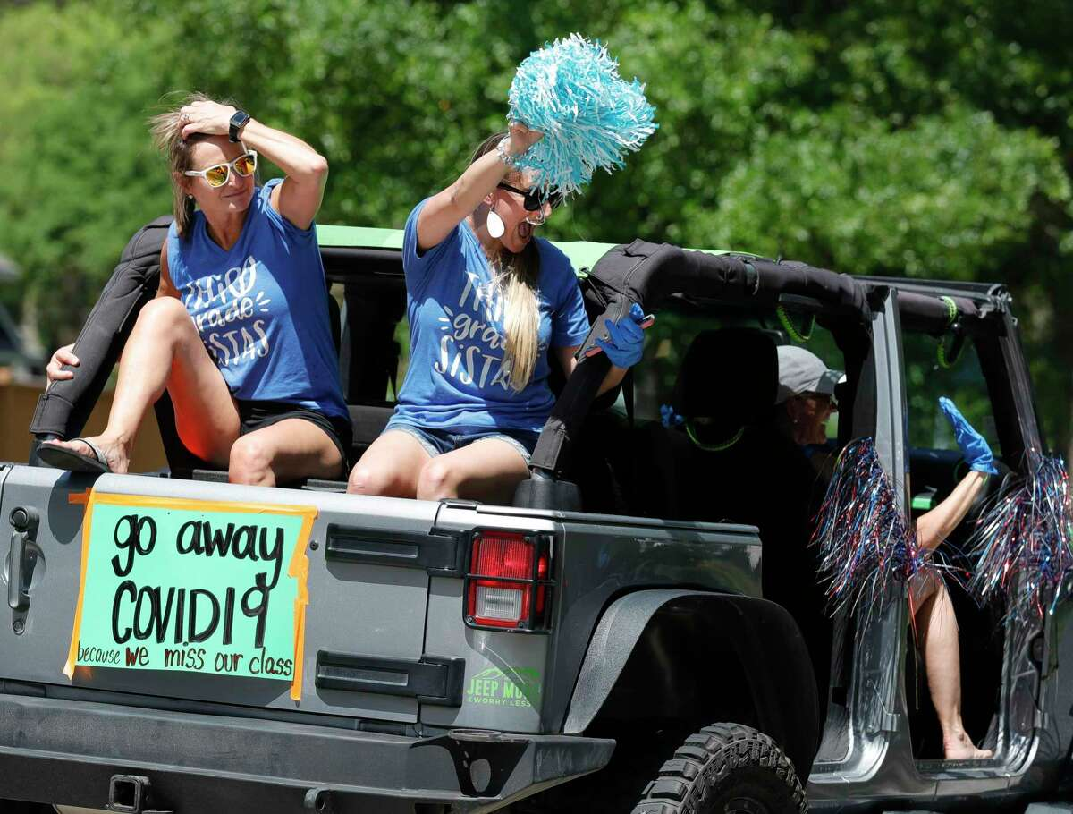 Kaufman Elementary School third grade teachers Ceri Brooks, left, and Brooke Baillie take part along with other teachers in a parade through nearby neighborhoods, Wednesday, March 25, 2020, in Spring.