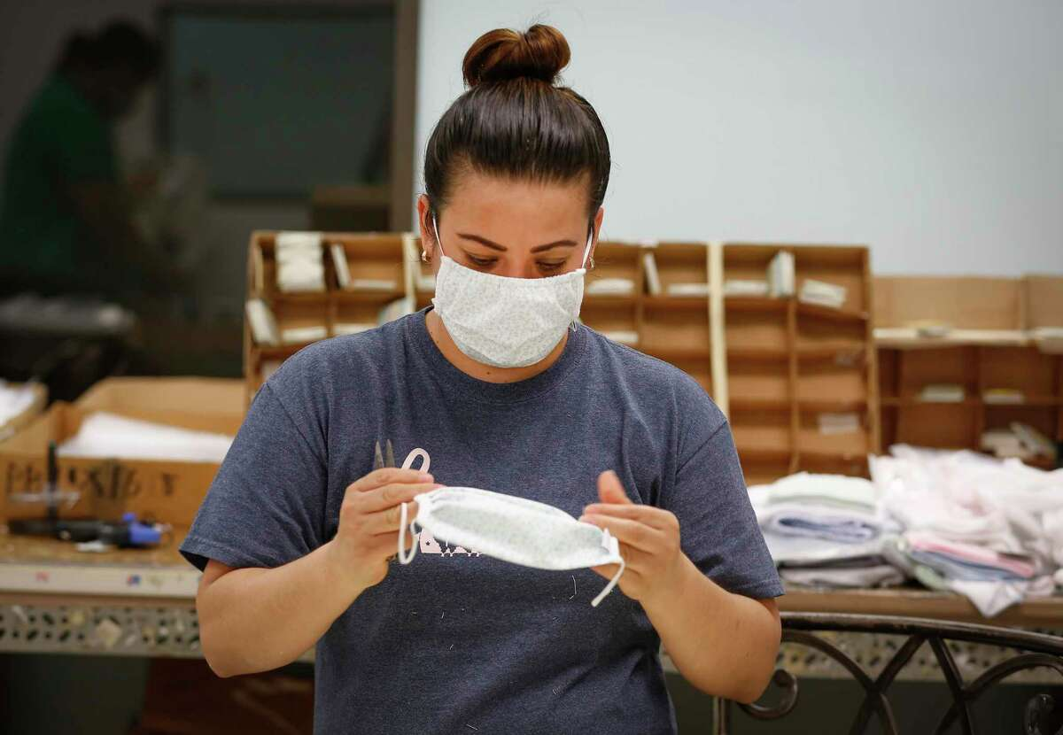 Maria Gonzalez inspects a face mask at Paty, Inc. Thursday, March 26, 2020, in Houston. Paty, Inc. has been manufacturing clothing for 65 years, but as the novel coronavirus has spurred demand for medical supplies, it has retooled its operations to produce face masks and surgical gowns.