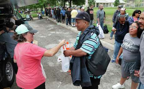 Judy Bittick, left, from Northside Church of Christ Loaves and Fishes Ministries, hands out a meal to an individual in line for food. Over 100 homeless individuals and some on limited income are fed by Northside Church of Christ Loaves and Fishes ministries, on Thursday, March 19, 2020 at Eduardo Garcia Park.