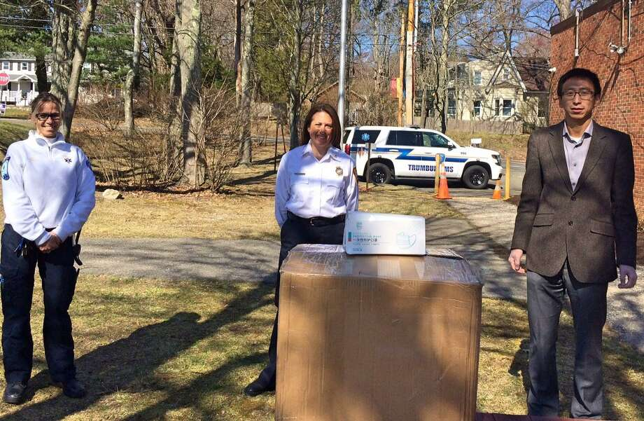 """EMS Director Leigh Goodman, left, and Fire Marshal Megan Murphy accept a donation of 1,700 protective masks from Jing """"Jack"""" Jiang of Trumbull, who made the donation on behalf of the town's Chinese-American community. Photo: Donald Eng / Hearst Connecticut Media"""