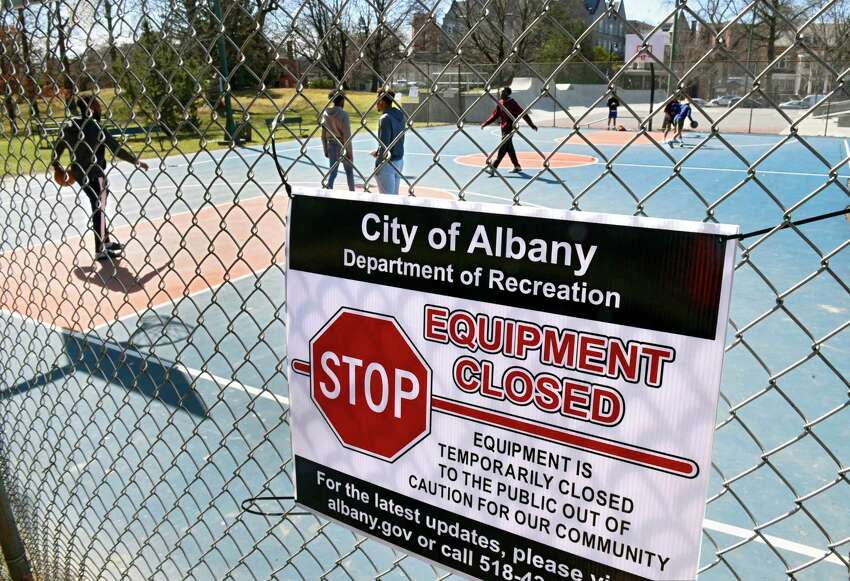 Young men continue to play basketball after Department of Recreation employees posted signs on the basketball equipment and surrounding fence at Washington Park informing the public not to use them on Friday, March 27, 2020 in Albany, N.Y. They told young men who were there alone they were fine. The city is discouraging groups of people playing basketball or other sports that involve close contact. (Lori Van Buren/Times Union)