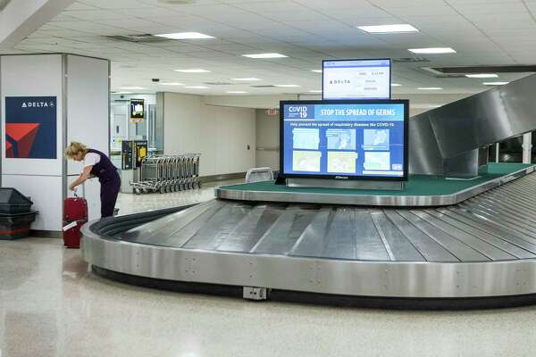 An airline worker picks up a bag in the baggage claim area of Terminal A at George Bush Intercontinental Airport on Wednesday, March 25, 2020 in Spring. Traffic and flight schedules at the airport has been cut drastically, due to coronavirus precautions.