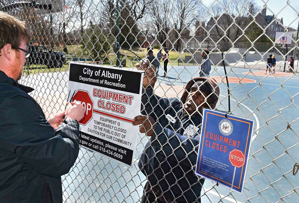 Department of Recreation employees Casey Craig, left, and Johnny White post signs on the basketball equipment at Washington Park informing the public not to use them on Friday, March 27, 2020 in Albany, N.Y. They told young men who were there alone they were fine. The city is discouraging groups of people playing basketball or other sports that involve close contact. (Lori Van Buren/Times Union)