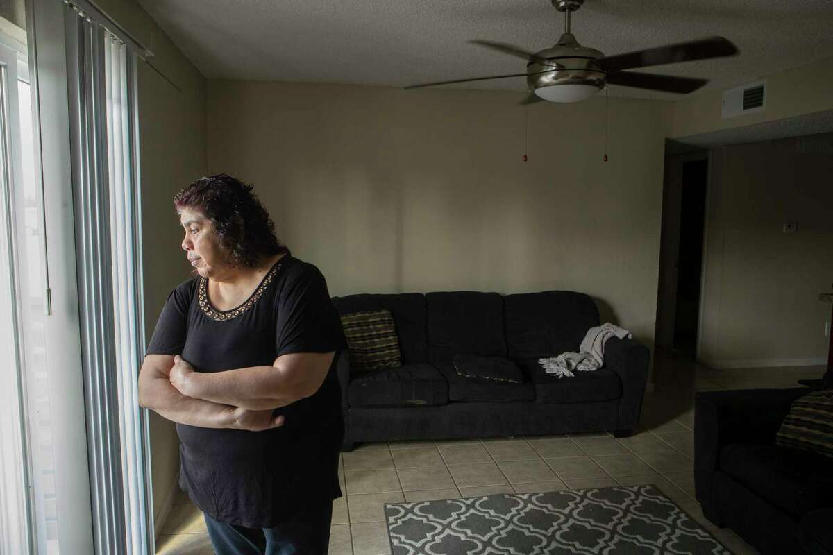 Anna Alvarez, who is a wheelchair attendant at George Bush Intercontinental Airport, stands in her apartment on Thursday, March 26, 2020 in Houston. She and two of her daughters, who all work at IAH, and have now seen their weekly paychecks slashed by at least 85 percent. Soon, she expects all three of them will be out of work since several of the major airlines have announced severe cutbacks beginning April 1.
