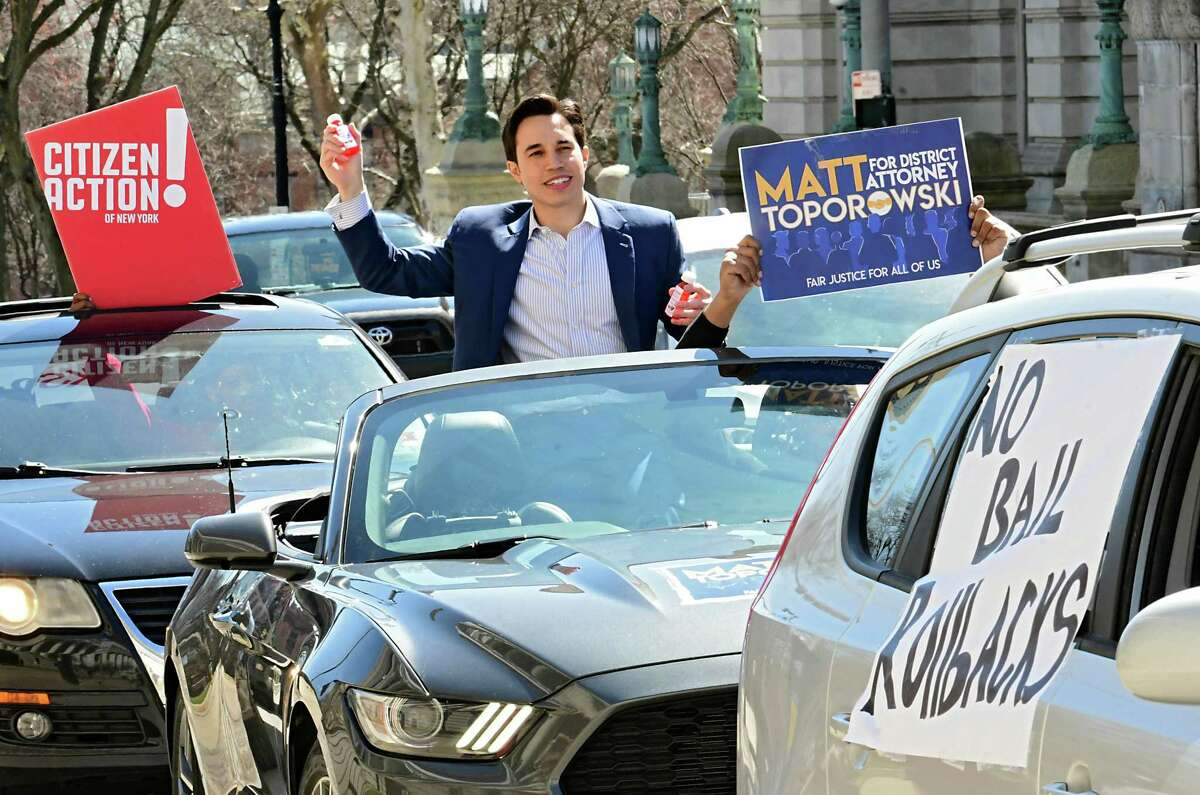District Attorney candidate Matt Toporowski throws bottles of hand sanitizer to people outside the New York State Capitol as he campaigns on Friday, March 27, 2020 in Albany, N.Y. People in his campaign made the hand sanitizer out of aloe vera gel and 91% alcohol. Toporowski is endorsed by Working Families and Citizen Action. (Lori Van Buren/Times Union)