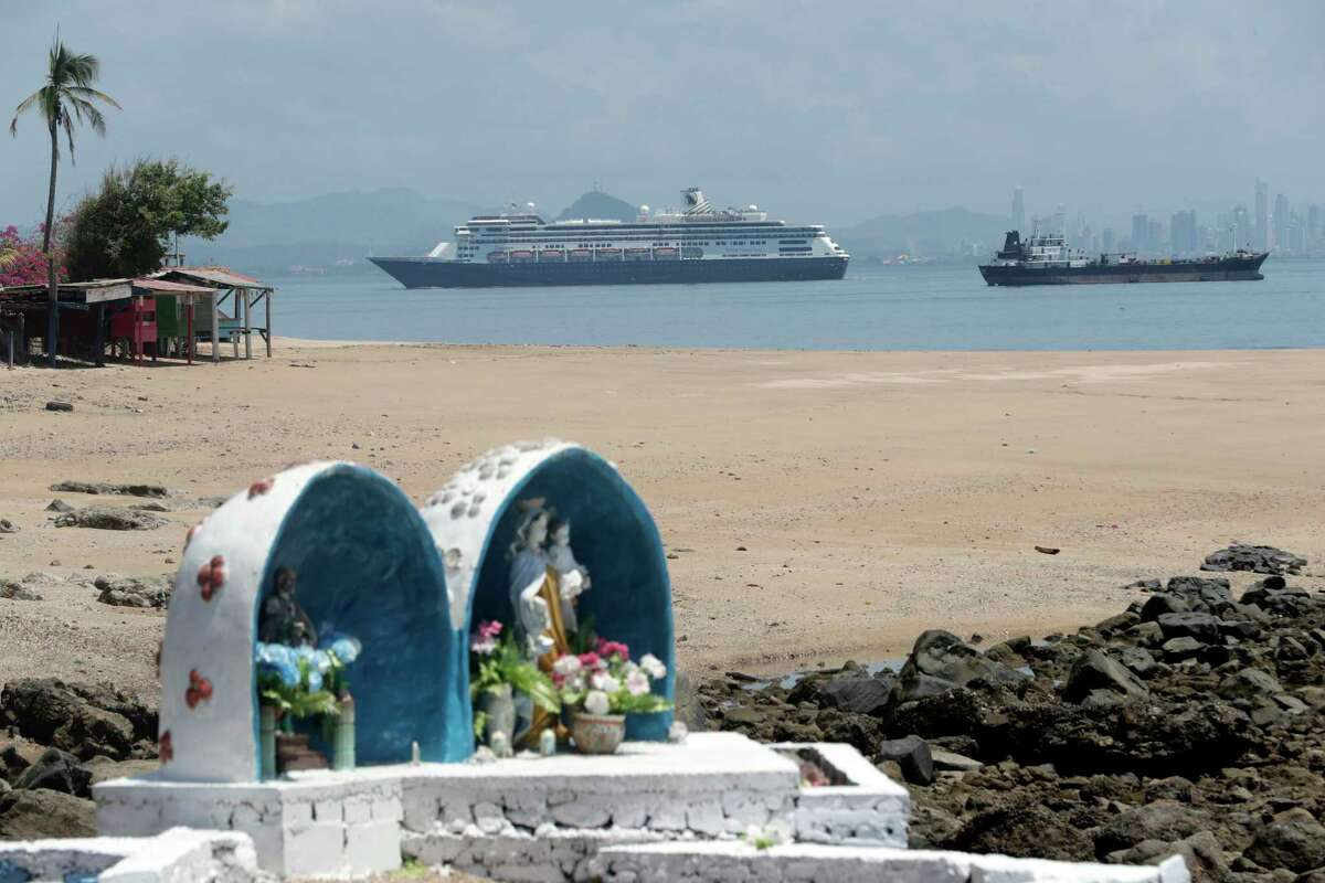 """The Zaandam cruise ship, top center, carrying dozens of guests with flu-like symptoms, arrives to the bay of Panama City, seen from Isla de Taboga, Panama, Friday, March 27, 2020, amid the worldwide spread of the new coronavirus. Once the vessel reaches Panamanian waters, health authorities are expected to board the ship to test passengers and decide whether it can cross the Panama Canal to head on towards Fort Lauderdale. On the beach in the foreground is a Catholic altar featuring Our Lady of Mount Carmel, or """"La Virgen del Carmen,"""" considered the patron saint of sailors."""