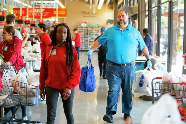 Niko Niko's owner Dimitri Fetokakis (left) brings in 80 boxed lunches ordered for employees of H-E-B, Friday, March 27, 2020, at the H-E-B Montrose Market in Houston.