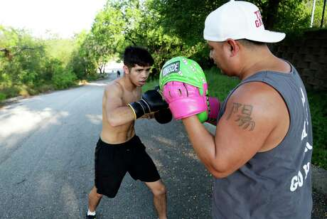 Gregory Morales works the mitts on top of the hill he runs up and down for Chato Martinez, right. Chato Martinez has been training his boxers outside at Brackenridge Park to stay in shape during the coronavirus restrictions.