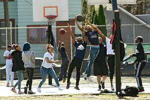 A large group of people are seen playing basketball at the Livingston and Lake Playground on Friday, March 27, 2020 in Albany, N.Y. Many people are still playing basketball in groups and not keeping a safe distance during the coronavirus outbreak. (Lori Van Buren/Times Union)