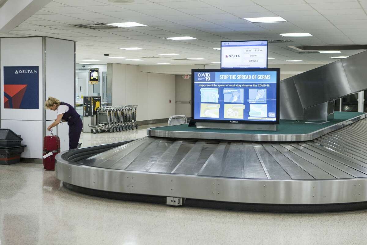 An airline worker picks up a bag in the baggage claim area of Terminal A at George Bush Intercontinental Airport on Wednesday, March 25, 2020 in Spring. Traffic and flight schedules at the airport has been cut drastically due to coronavirus precautions, resulting in furloughs and layoffs for many airport workers at IAH.