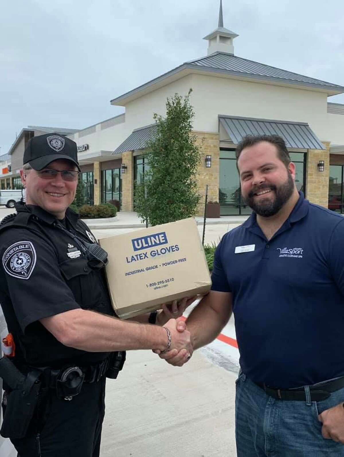 Fort Bend County Constable's Office Precinct 3 Deputy Shawn Stillabower accepts a glove donation from Thomas Westbrook, VillaSport general manager.