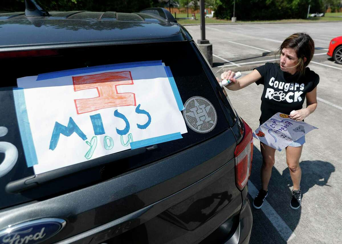 Kindergarten teacher Jamie Rodgers decorates her car as teachers with Kaufman Elementary School take part in a parade through nearby neighborhoods, Wednesday, March 25, 2020, in Spring.