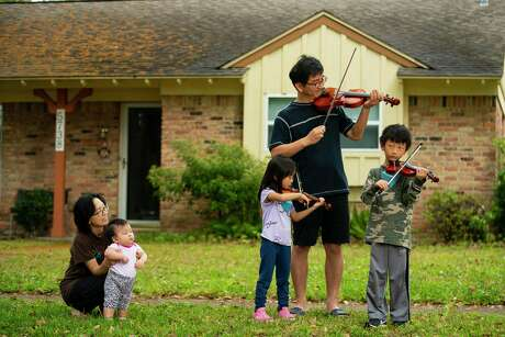 The Yun family plays together, Tuesday, March 17, 2020, in the Westbury neighborhood of Houston. Parker Elementary School cello teacher Lisa Vosdoganes encouraged students at the HISD music magnet to take to their individual front yards at 10 am Tuesday morning to play together, apart.