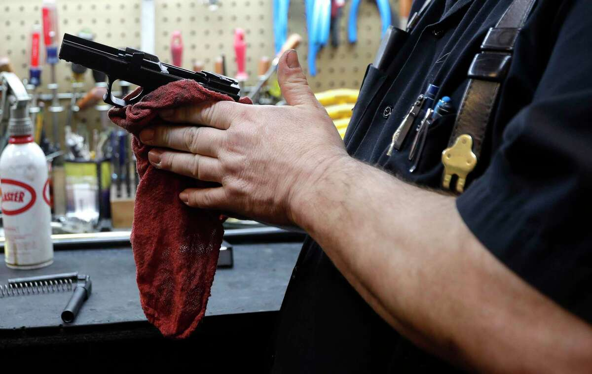Allen Perry, owner of Mac Daddy's Cigars and Guns, cleans and repairs a Springfield XDM, Wednesday, March 18, 2020, in Conroe.