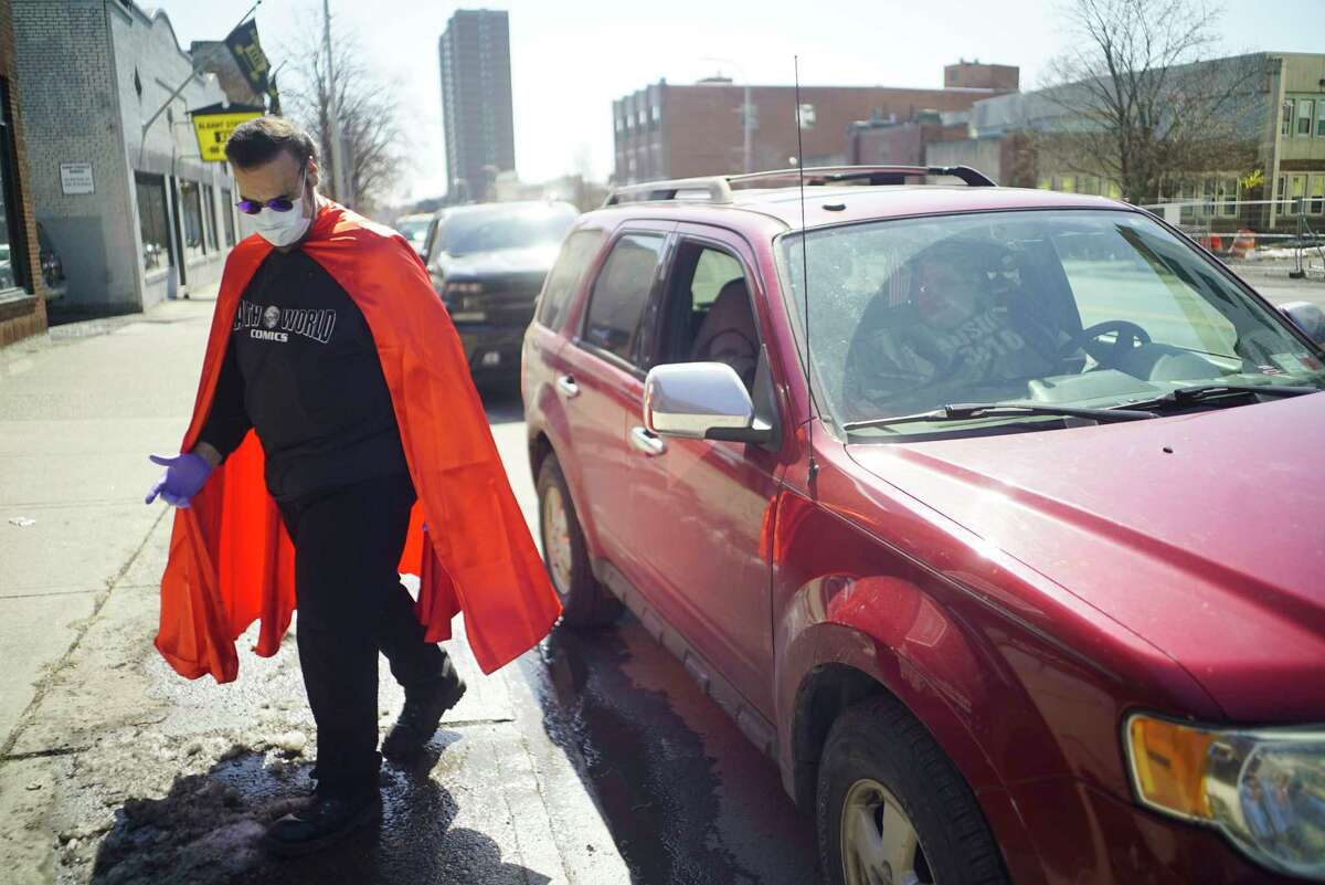 J.C. Glindmyer, owner of Earthworld comics, walks away after delivering comic books to a customer who drove up to the curb on Thursday, March 26, 2020, in Albany, N.Y. Glindmyer started doing curbside delivery to customers on Wednesday, the day new releases come out. He said that customers should email the shop or reach out through the shop's Facebook page or Instagram account to place an order. Glindmyer said that he opened the comic book store in 1983 and is just trying to get comics into the hands of his customers as they are staying home. The shop will be doing curbside delivery till 6pm on Friday and 5pm and Saturday, then customers should check the website or Facebook page for information on what days they will be open next week. (Paul Buckowski/Times Union)