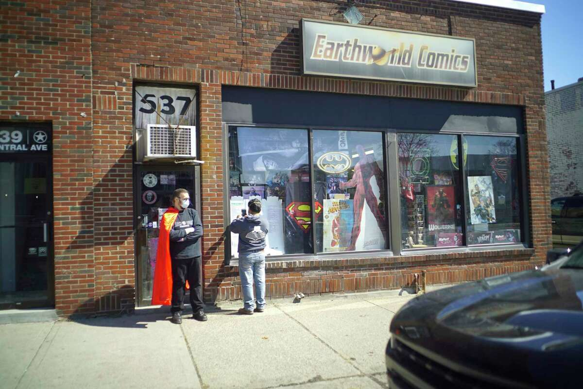 J.C. Glindmyer, left, owner of Earthworld comics, talks with a customer who looks over the new releases listed on a board in the window of the shop on Thursday, March 26, 2020, in Albany, N.Y. Glindmyer started doing curbside delivery to customers on Wednesday, the day new releases come out. He said that customers should email the shop or reach out through the shop's Facebook page or Instagram account to place an order. Glindmyer said that he opened the comic book store in 1983 and is just trying to get comics into the hands of his customers as they are staying home. The shop will be doing curbside delivery till 6pm on Friday and 5pm and Saturday, then customers should check the website or Facebook page for information on what days they will be open next week. (Paul Buckowski/Times Union)