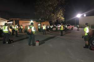 Waste Management employees in Houston practice social distancing at 5 a.m. March 26 as they gather before heading out to collect waste.