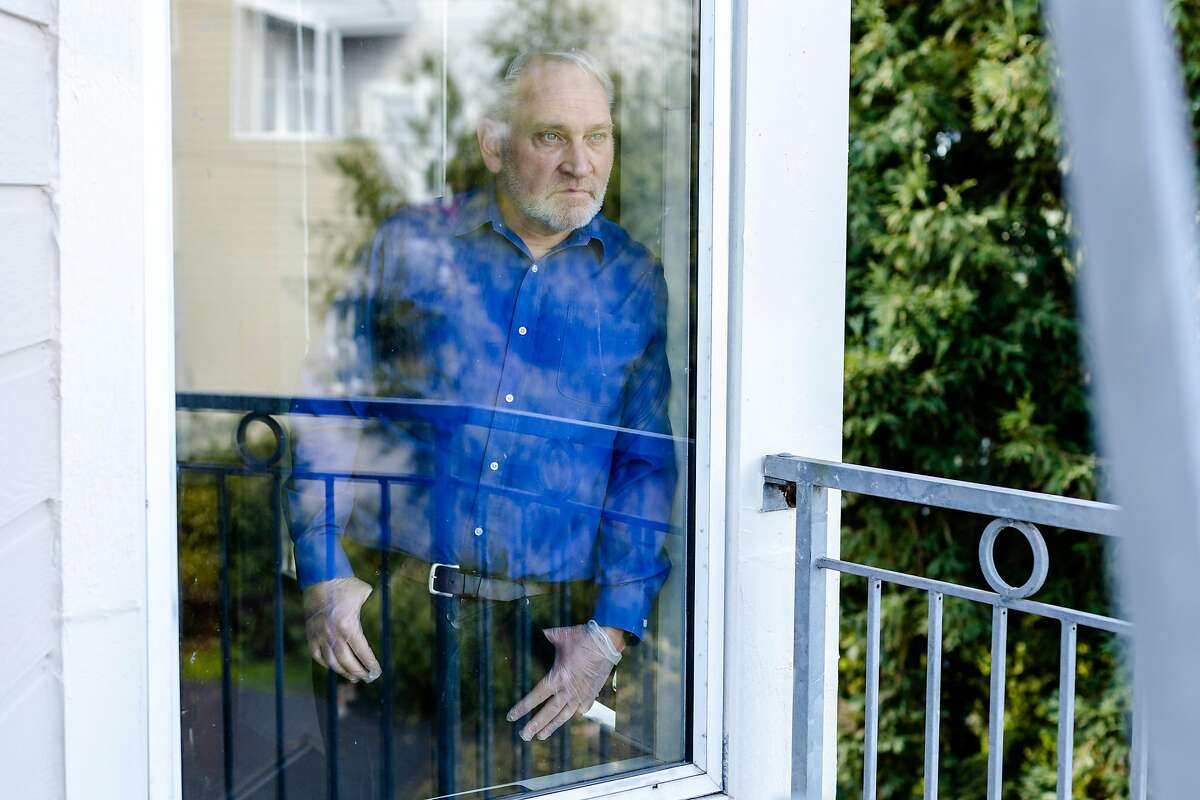 Carl Jaeger looks out of a window in his home on Friday, March 27, 2020, in San Francisco, Calif. Mr. Jaeger, who is an Airbnb host in San Francisco, is facing financial uncertainty as Airbnb cancellations continue due to the coronavirus pandemic.
