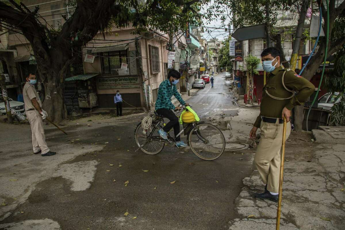 NEW DELHI, INDIA - MARCH 27: An Indian man rides his bicycle as Indian policemen stand guard on a deserted commercial hub to enforce a lockdown order by the government as a preventive measure against the COVID-19 on March 27, 2020 in New Delhi, India. India is under a 21-day lockdown to fight the spread of the virus and while security personnel on the roads are enforcing the restrictions in many cases by using force, the workers of the country's unorganized sector are bearing the brunt of the curfew-like situation. According to international labour organisations 90 percent of India's workforce is employed in the informal sector and most do not have access to pensions, sick leave, paid leave or any kind of insurance. Reports on Thursday said that Prime Minister Narendra Modi's government is preparing a massive bailout for the underprivileged sections of the country and will hand over the aid through direct cash transfers. (Photo by Yawar Nazir/Getty Images)
