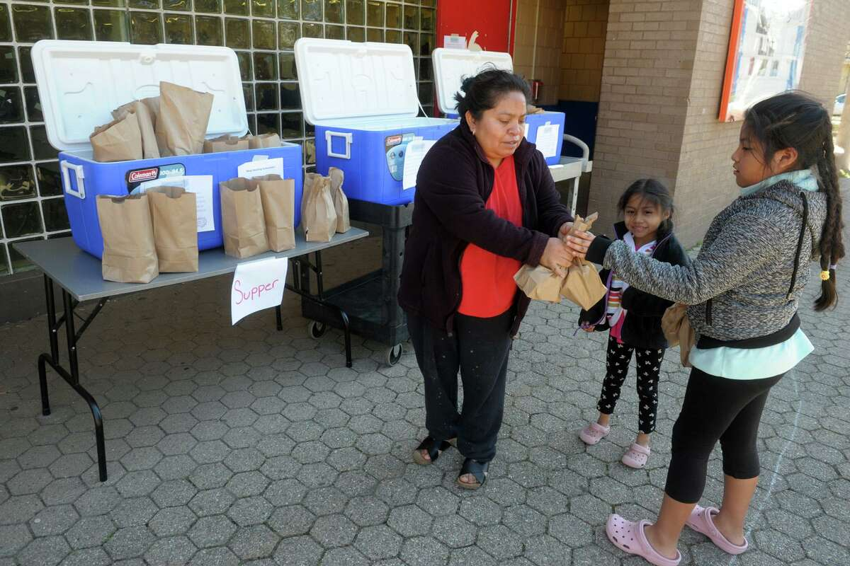 Maria Mecatl picks up grab-and-go meals with her nieces, Isabella and Heidi Valez, at Curiale School in Bridgeport, Conn. March 27, 2020. Bridgeport schools have expanded the program from breakfast and lunch to also include items for dinner meals.