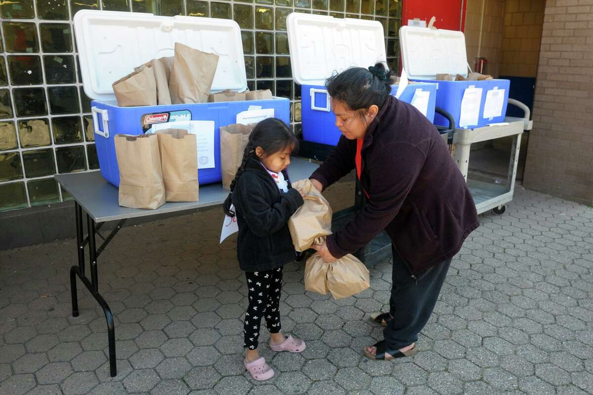 Maria Mecatl picks up grab-and-go meals with her niece, Isabella Valez, at Curiale School in Bridgeport, Conn. March 27, 2020. Bridgeport schools have expanded the program from breakfast and lunch to also include items for dinner meals.