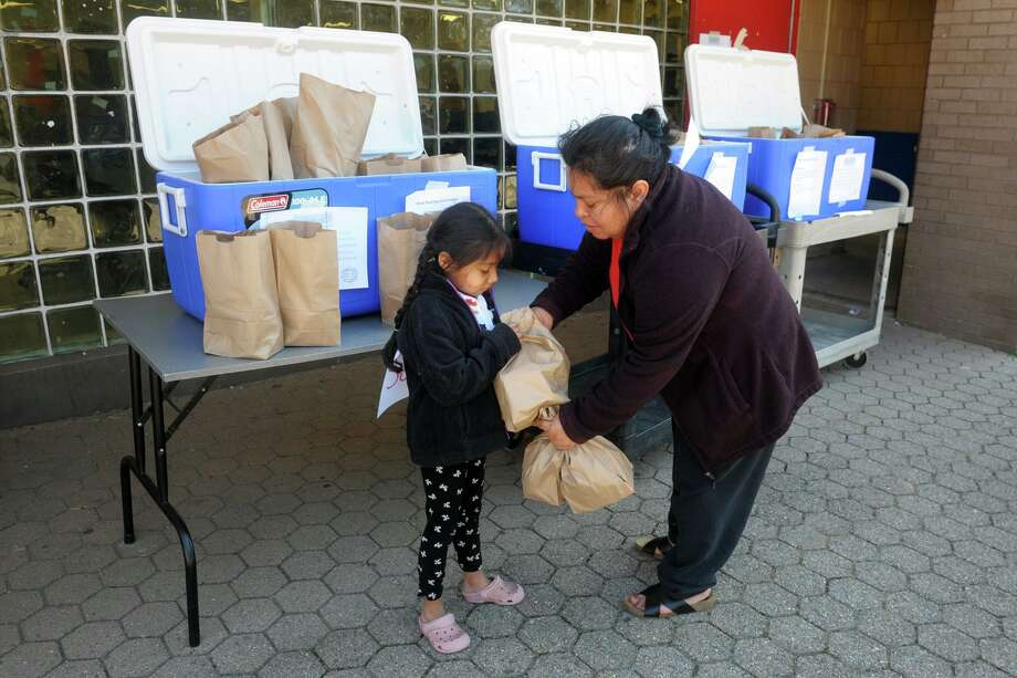 Maria Mecatl picks up grab-and-go meals with her niece, Isabella Valez, at Curiale School in Bridgeport, Conn. March 27, 2020. Bridgeport schools have expanded the program from breakfast and lunch to also include items for dinner meals. Photo: Ned Gerard / Hearst Connecticut Media / Connecticut Post