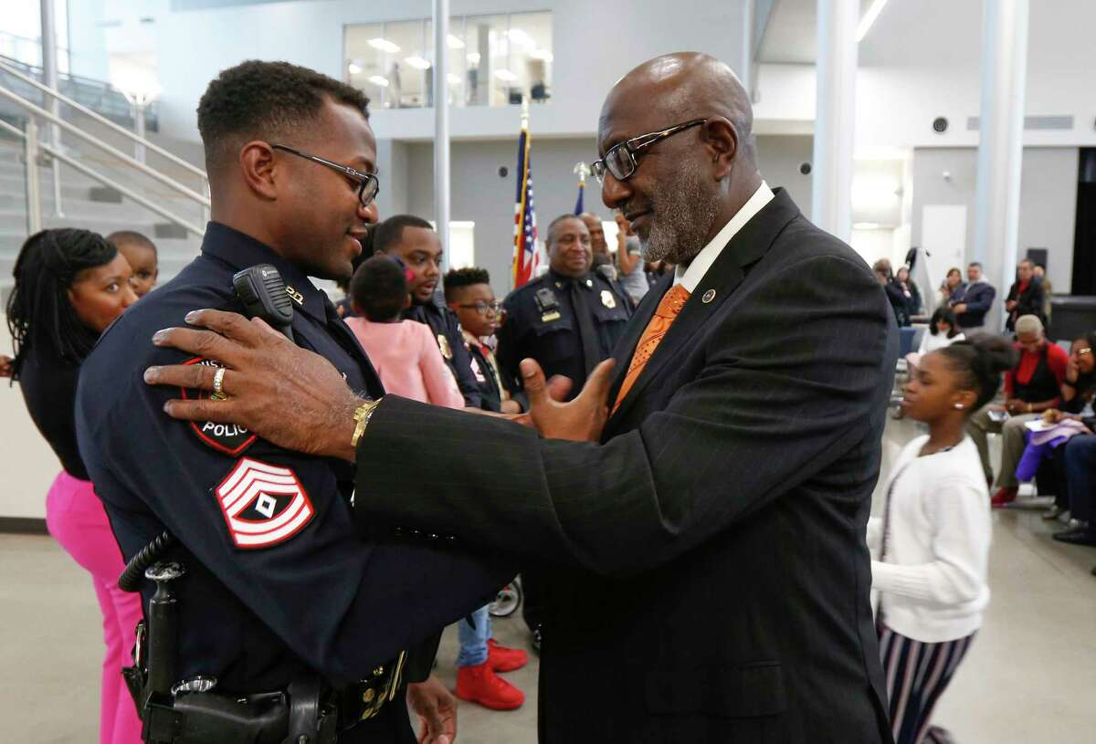 Newly sworn in HISD Police Sgt. Justin Williams shakes his father's, Willie Williams, hand after the elder Williams pinned his badge on him in a formal swearing-in ceremony at the High School for Law and Justice Wednesday, Jan. 23, 2019, in Houston. The HISD Police Department celebrated the promotion of six sergeants and seven officers at the event.